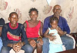Chidiebere und Chidinme Obodo (Zwillinge) mit Vater Fidelis und dessen Enkelin. Die Familie lebt zu zehnt in einem kleinen Zimmer