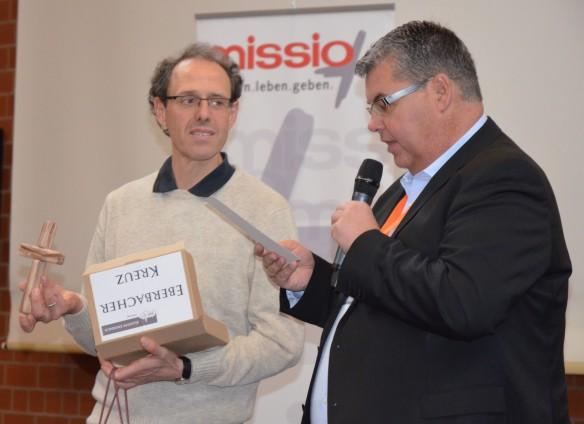 Daniel Rick (rechts) bedankt sich bei Diakon Mathias Wolf aus Oberursel mit einem Eberbacher Kreuz für seine Prozessbeobachtung