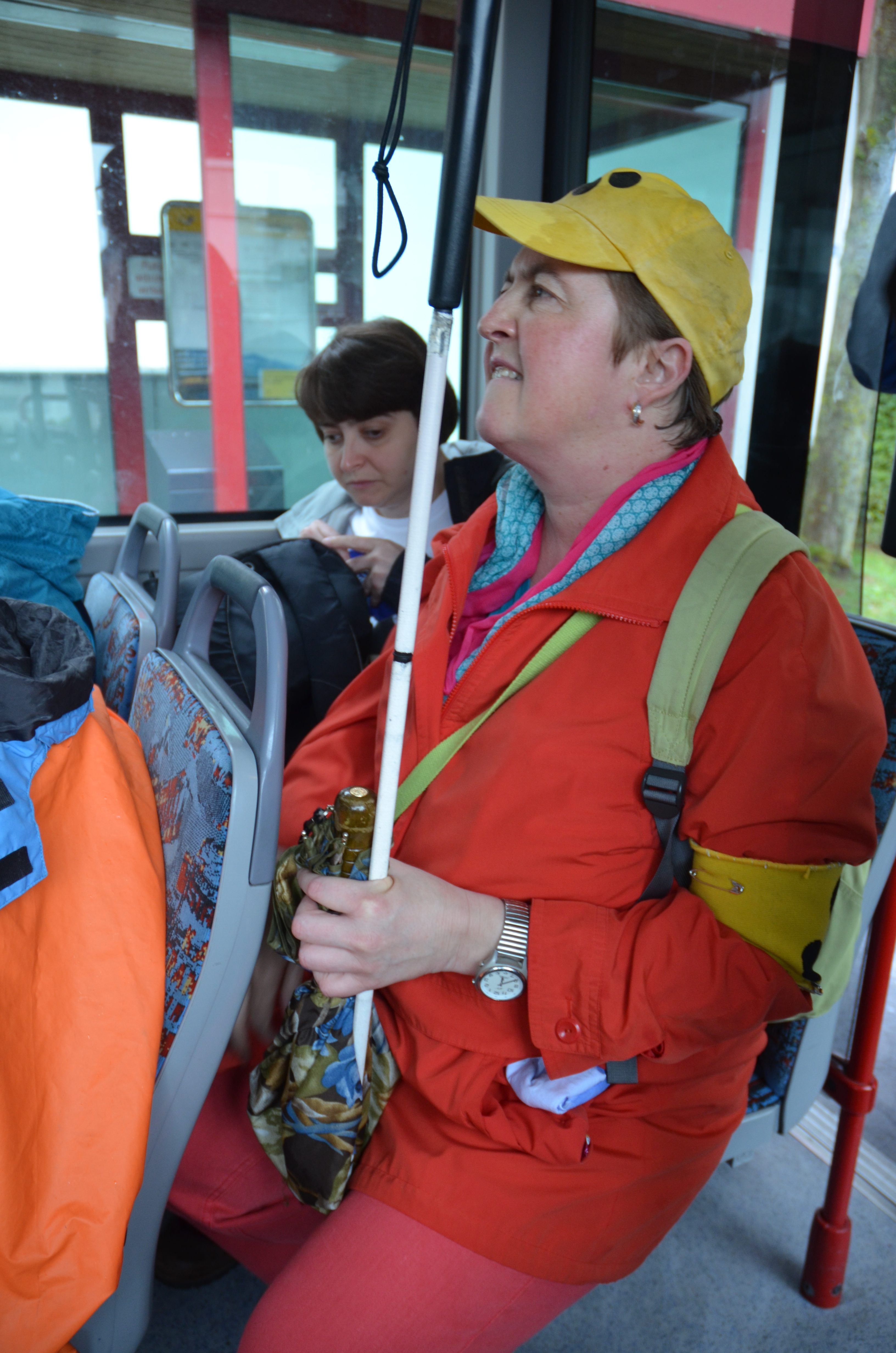 Sabine hat den weißen Stock dabei und trägt eine gelbe Kappe mit schwarzen Punkten und die passende Armbinde.